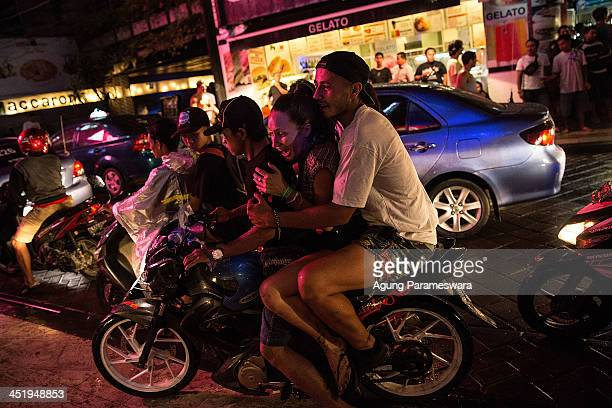 Two teenagers ride a motorbike taxi during Australian 'schoolies' celebrations following the end of the year 12 exams at Legian street on November 25...