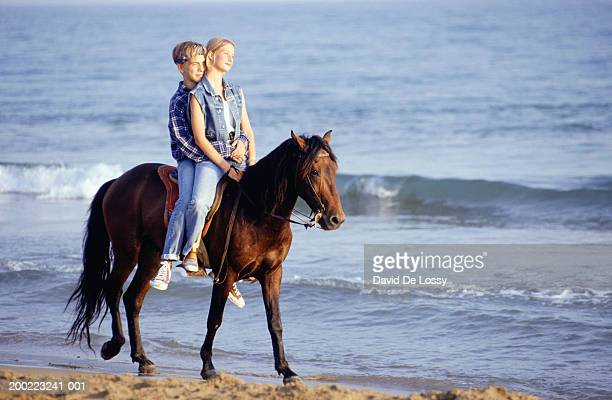 two teenagers (14-15) riding horse on beach - one animal stock pictures, royalty-free photos & images