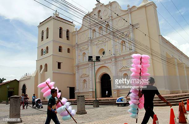 Two teenagers sell candy known as ''algodones de azucar'' in front of the cathedral at the Comayagua park, some 110 kms north of Tegucigalpa, on June...