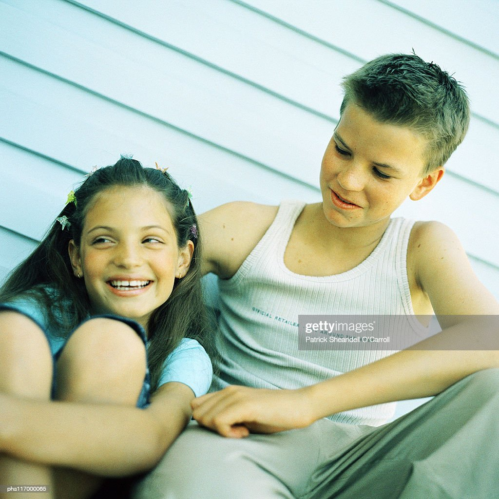 Two teenagers sitting side by side, outside : Stockfoto