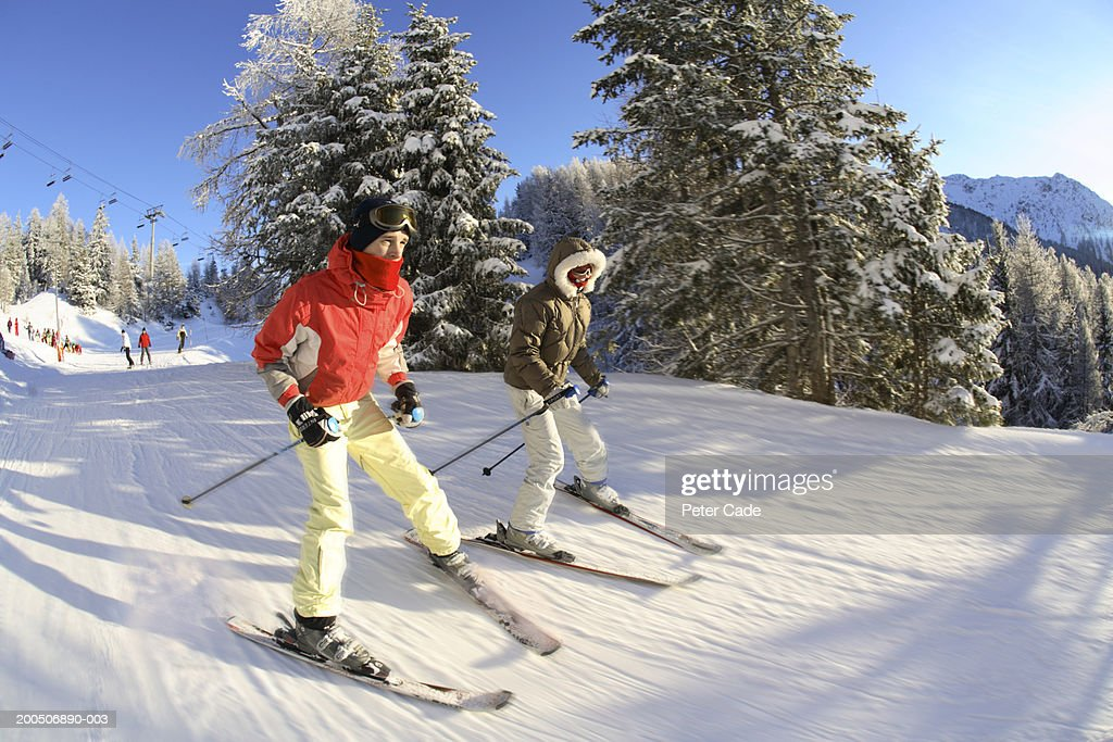 Two teenagers (16-18) skiing, side view, (wide angle, blurred motion) : Stock Photo