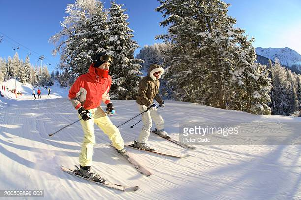 Two teenagers (16-18) skiing, side view, (wide angle, blurred motion)
