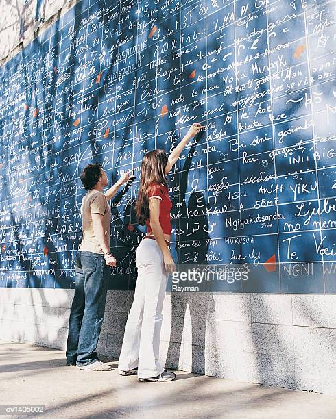 Two Teenagers Stand in Front of Mural Pointing at Words