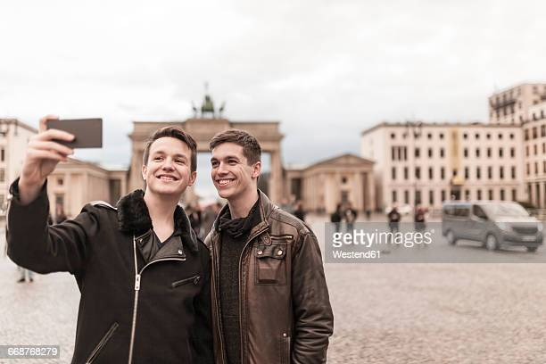 Two teenagers taking a smartphone image of themselves in front of the Brandenburg Gate in Berlin