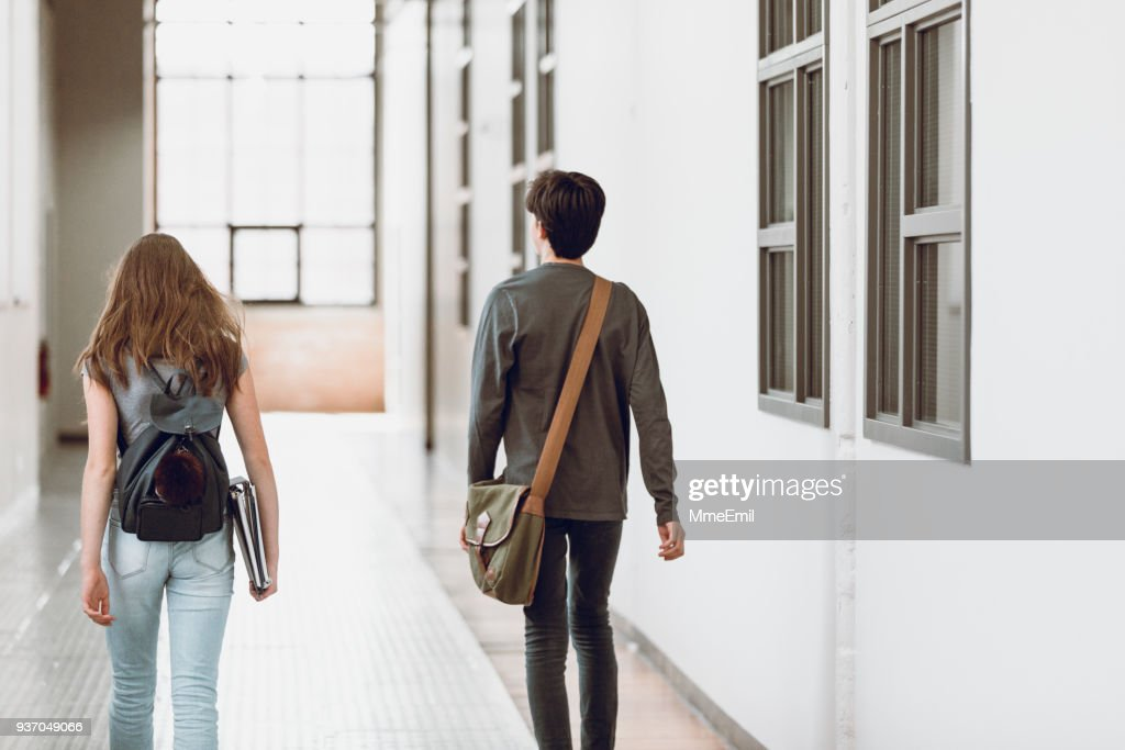 Two teenagers walking in the corridor at school. Rear view. One boy and one girl : Stock Photo