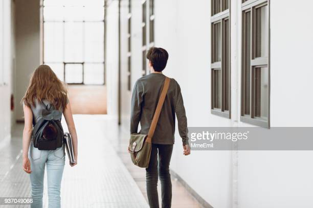 two teenagers walking in the corridor at school. rear view. one boy and one girl - high school musical: the musical: the series stock pictures, royalty-free photos & images