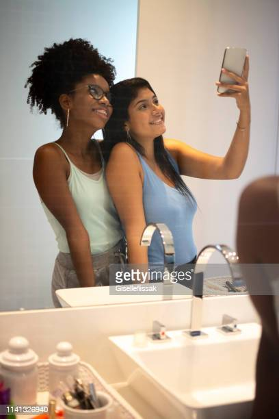 two teenages girls, taking selfies in front of the mirror in the bathroom. - mirror selfie stock pictures, royalty-free photos & images