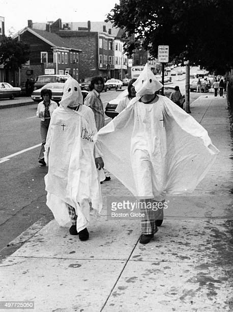 Two teens impersonating Ku Klux Klan members dressed in white sheets and pointed hoods walk down Dorchester Street near Old Colony Avenue in Boston...