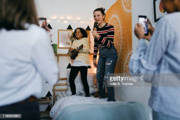 two teens singing and playing guitar - filmen stockfoto's en -beelden