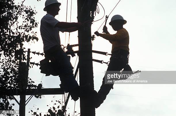 Two telephone repairmen working on pole in Ojai California