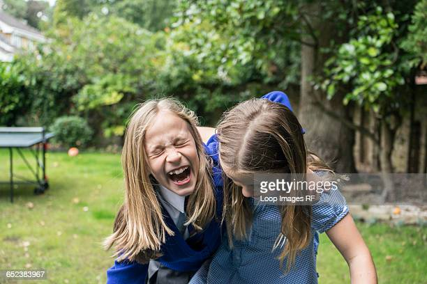 Two ten year old girls in school uniform laughing together outside