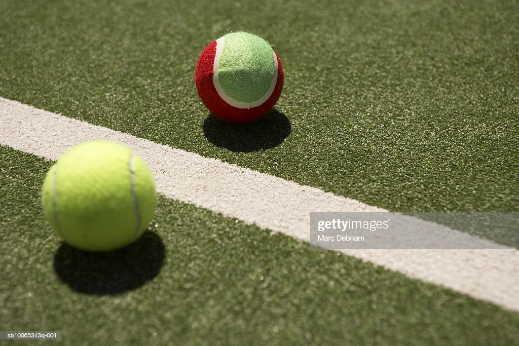 Two tennis balls beside line on court : Foto stock