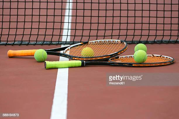 Two tennis rackets and four balls lying on ground of tennis court