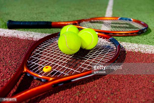 two tennis rackets on court with three tennis balls on one - tennis racket stock pictures, royalty-free photos & images
