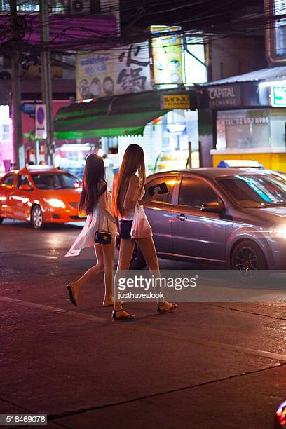 two thai ladyboys are crossing street - ladyboys stock pictures, royalty-free photos & images