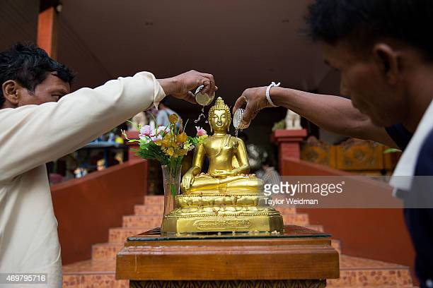 Two Thai men pour offerings of scented water over a buddha statue during the Songkran festival on April 15 2015 in Chiang Mai Thailand The Songkran...