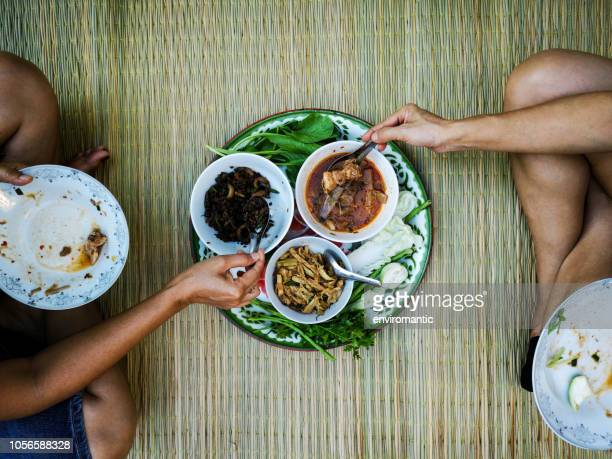 two thai women sit on a reed mat traditionally eating a selection of freshly cooked northern thai food. - tradizione foto e immagini stock