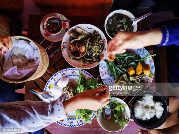 two thai women traditionally eating a selection of freshly cooked northern thai food of vegetables, soups and curries served in dishes on a wooden table, along with sticky rice, which is a food staple in northern and northeast thailand. - chiang mai province stock photos and pictures