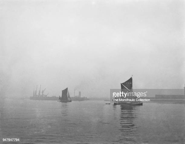 Two Thames barges passing dock cranes on the waters at Sheerness a town beside the mouth of the River Medway on the north west corner of the Isle of...