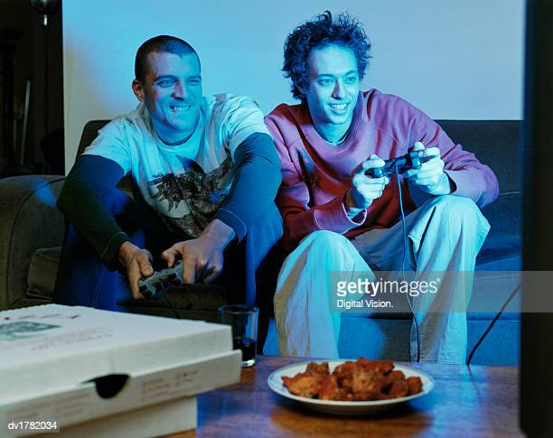 Two Thirty something Men Sitting in a Living Room Playing a Games Console
