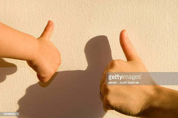 Two thumbs up, adult and child's hands