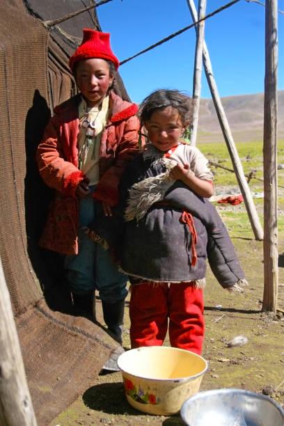 Two Tibetan sisters standing near their Yurt