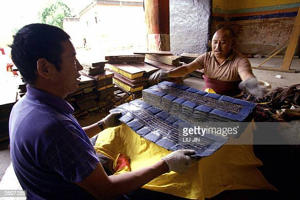 Two Tibetan workers prepare to wrap the fivehundred history scriptures after cleaning at an entrance of main chapel of the Pelkor Chode monastery in...