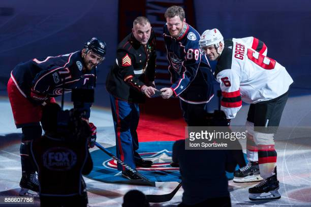 Two time NASCAR Daytona 500 winner Dale Earnhardt Jr and Marine Seargent Sean Landis drop the honorary puck with Columbus Blue Jackets left wing Nick...
