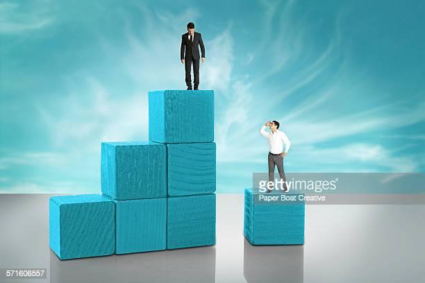 two tiny businessmen on wooden blocks - comparação - fotografias e filmes do acervo