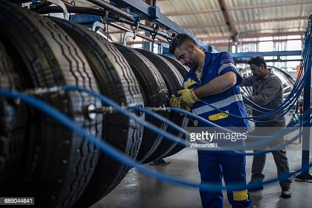 Two tire repairmen filling up air in tire valves