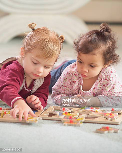 Two toddler girls (18-21 months) lying on floor, playing with puzzles