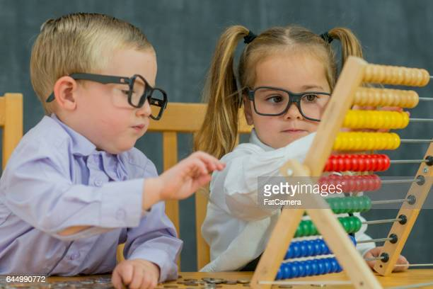 Two toddlers are dressed up as business adults and are playing on an abacus.