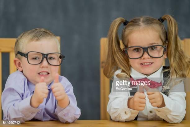 2 つの幼児ビジネス大人として服を着ています。彼らが彼らの親指を保有しているとカメラを見ながら笑っています。