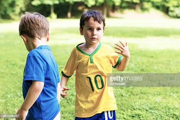 due bambini avendo una discussione durante la partita di calcio - pjphoto69 foto e immagini stock