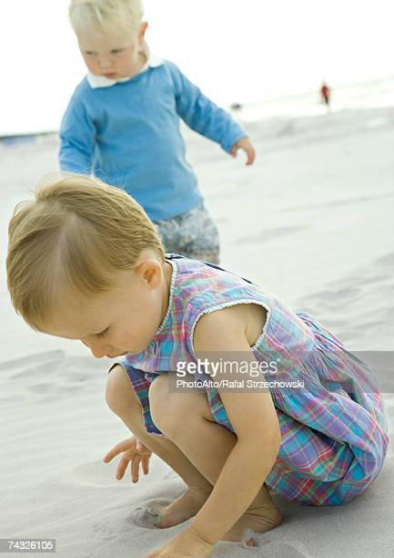 Two toddlers playing on beach