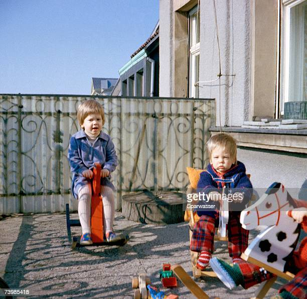 Two toddlers playing on rocking horses on balcony