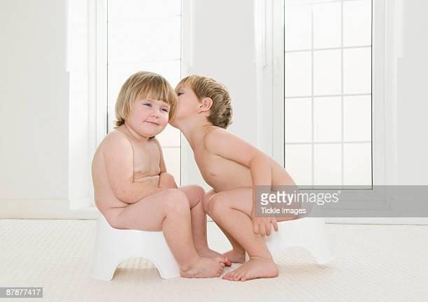 two toddlers sitting on potties. - chico desnudo cuerpo entero fotografías e imágenes de stock