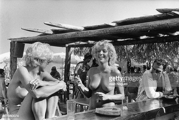 Two topless women talk at the counter of La Voile Rouge beach bar on a StTropez beach