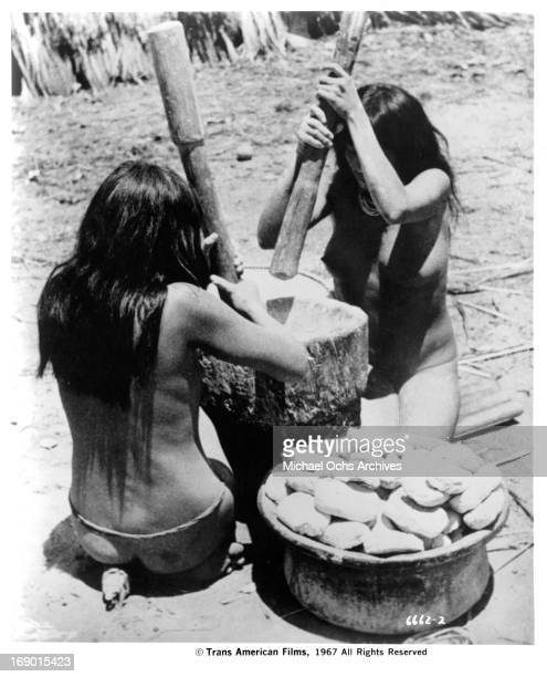 Two topless young native women make food for their tribe in a scene from the documentary film 'Macabro' 1967