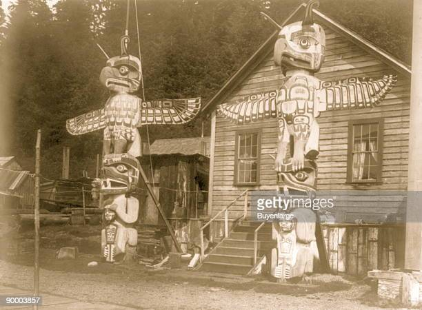 Two totem poles in front of a wood frame house in the Nimkish village Yilis on Cormorant Island Totem pole depicts an eagle representing the owner's...