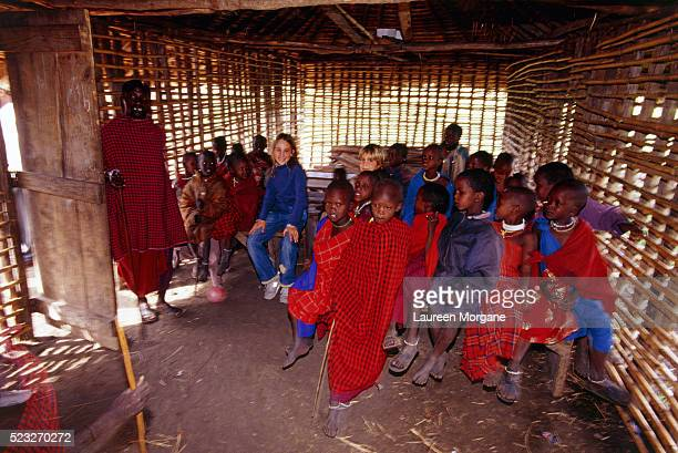 two tourist children among masai school class, masai village, (ngorongoro), tanzania, africa - traditional clothing stock pictures, royalty-free photos & images