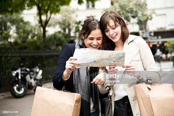 Two tourist girls looking at a map on streets in Paris