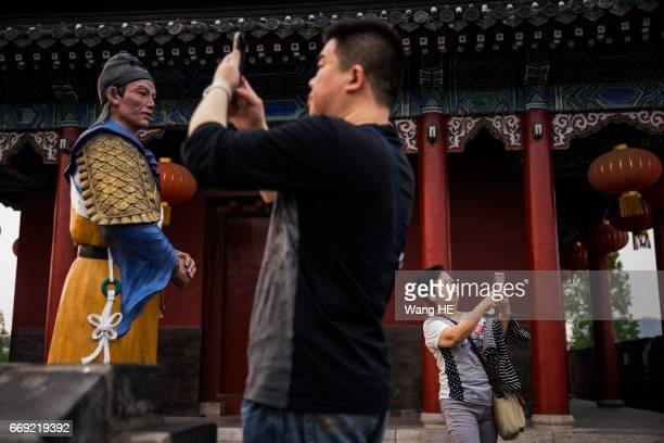 Two Tourist use iPhone take pictures in Ancient City on April 152017 in jingzhouHubei provinceChinaJingzhou with a history of more than 2600 years is...