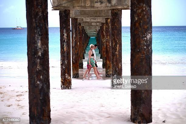 Two tourist walk under a jetty as they stroll along a beach in Bridgetown, Barbados on May 4, 2015. AFP PHOTO/JEWEL SAMAD
