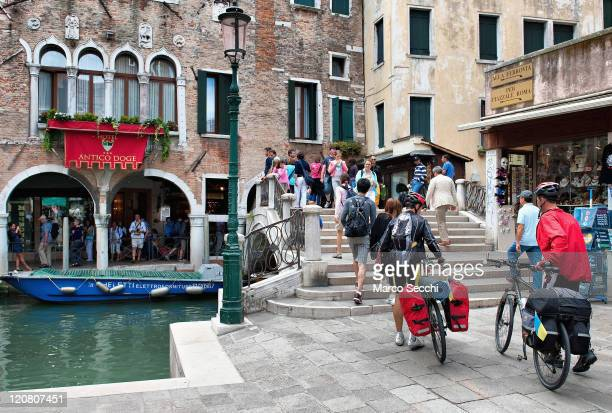 Two tourists approach a bridge walking with their bikes as it is not permitted to ride a bike in Venice on August 11 2011 near the Rialto area in...