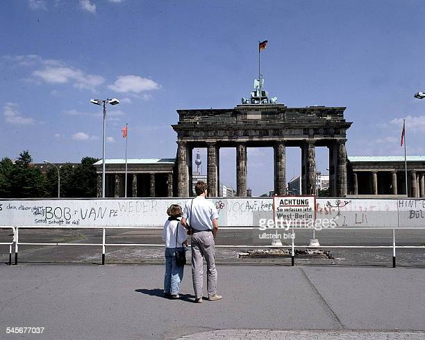 Two tourists at the Berlin Wall by the Brandenburg Gate