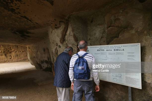 Two tourists in front of the entrance to the cave of the Sibilla Cumana, the priestess of Apollo, one of the most important Sibyls, prophetic figures...