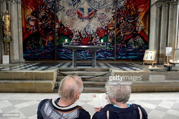 Two tourists look at The Benker Schirmer Tapestry the retroquire Chichester Cathedral West Sussex in Chichester Cathederal