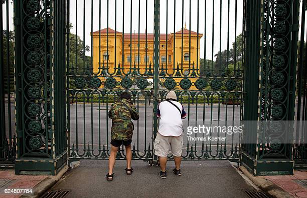 Two tourists photographed through the entrance gate of the Presidential Palace in Hanoi on October 31 2016 in Hanoi Vietnam