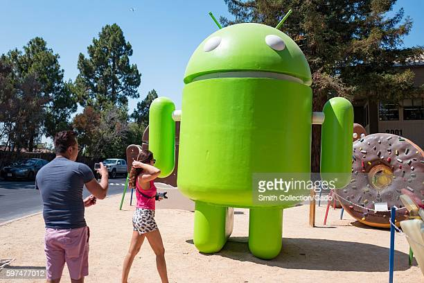 Two tourists prepare to take photographs in front of a large statue representing the Android cellphone operating system at the Googleplex...